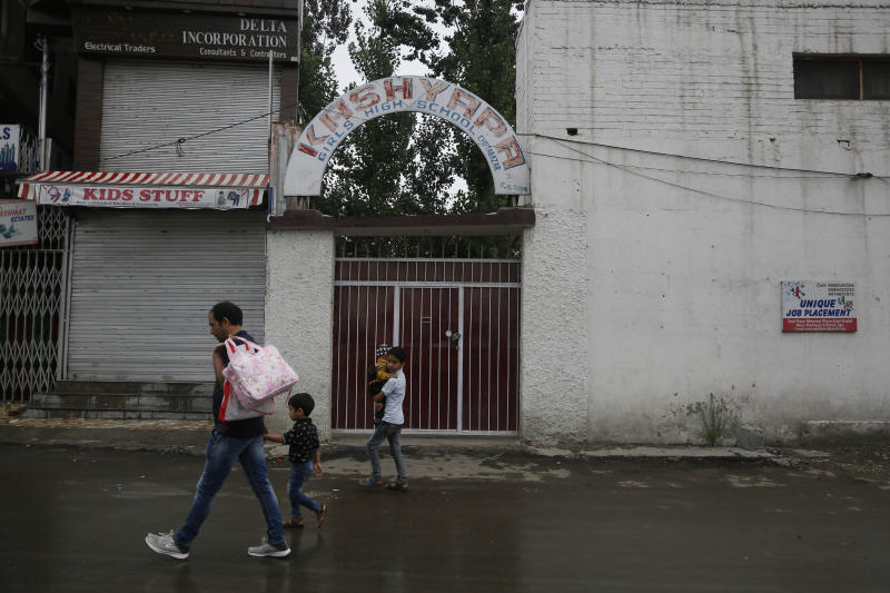 Kashmiris walk outside a closed school in Srinagar, Indian controlled Kashmir, Monday, Aug. 19, 2019. Restrictions continue in much of Indian-administered Kashmir, despite India's government saying it was gradually restoring phone lines and easing a security lockdown that's been in place for nearly two weeks. (AP Photo/Mukhtar Khan)