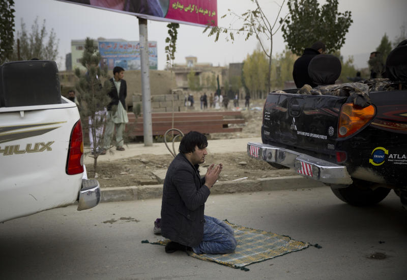 An Afghan man prays between two police cars near the scene of a powerful suicide vehicle bomb on the outskirts of Kabul, Afghanistan, Saturday, Nov. 16, 2013. The deadly bomb targeted a site where thousands of elders are to gather next week to discuss a controversial security agreement with the United States, which would allow U.S. troops to remain in Afghanistan after the final withdrawal of international combat troops at the end of 2014, officials said. (AP Photo/Anja Niedringhaus)