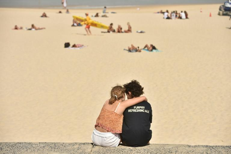 """A couple gets close on Bondi Beach -- """"this is about saving lives,"""" New South Wales state Police Minister David Elliott said of the lockdown (AFP Photo/PETER PARKS)"""