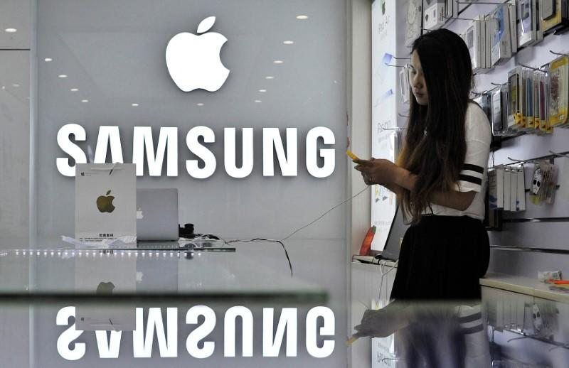 FILE PHOTO: A sales assistant uses her mobile phone next to the company logos of Apple and Samsung at a store in Hefei