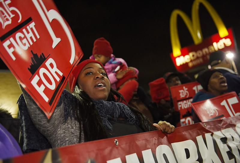 People protest to raise the minimum wage in front of a McDonald's.