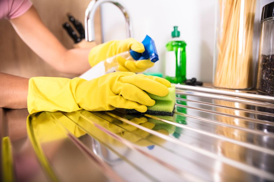 Close-up Of Person's Hand Wearing Yellow Gloves Cleaning Stainless Steel Sink With Sponge
