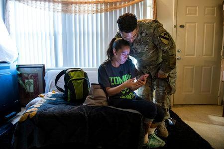 FILE PHOTO: Leanne Bell, 39, and her husband Spc. Tevin Mosley, 26, react to local residents posts regarding mold and housing related issues on a community Facebook group at the army base housing allocated to their family in Fort Hood, Texas, U.S. May 16, 2019. Bell and her family say they are vacating the home immediately after Mosley's military service contract expires in May. Since moving into the home 3 years ago, the family says they have experienced severe breathing issues, rashes, depression and hair loss, they believe is attributed to a mold infestation. REUTERS/Amanda Voisard