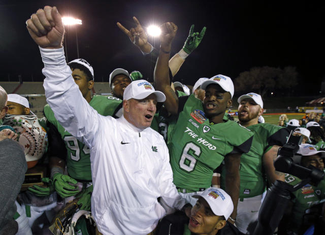 FILE - In this Dec. 16. 2017, file photo, Marshall players and coach Doc Holliday celebrate after their 31-28 victory over Colorado State in the New Mexico Bowl NCAA college football game in Albuquerque, N.M. Marshall goes into Hollidays 10th season as the favorite in Conference USA's West Division. The Thundering Herd won four of their final five games last season, including their seventh consecutive bowl victory. (AP Photo/Andres Leighton, File)