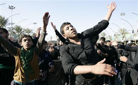 Shi'ite pilgrims beat their chests in a ceremony to mark the religious ritual of Arbaeen in Kerbala, about 80 km (50 miles) southwest of Baghdad, December 24, 2013. REUTERS/Mushtaq Muhammed