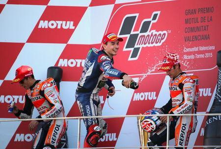 Spanish new World Champion Yamaha MotoGP rider Jorge Lorenzo (C) celebrates between Spanish Honda riders Marc Marquez (L) and Dani Pedrosa after winning the Valencia Motorcycle Grand Prix at the Ricardo Tormo racetrack in Cheste, near Valencia, November 8, 2015. REUTERS/Heino Kalis