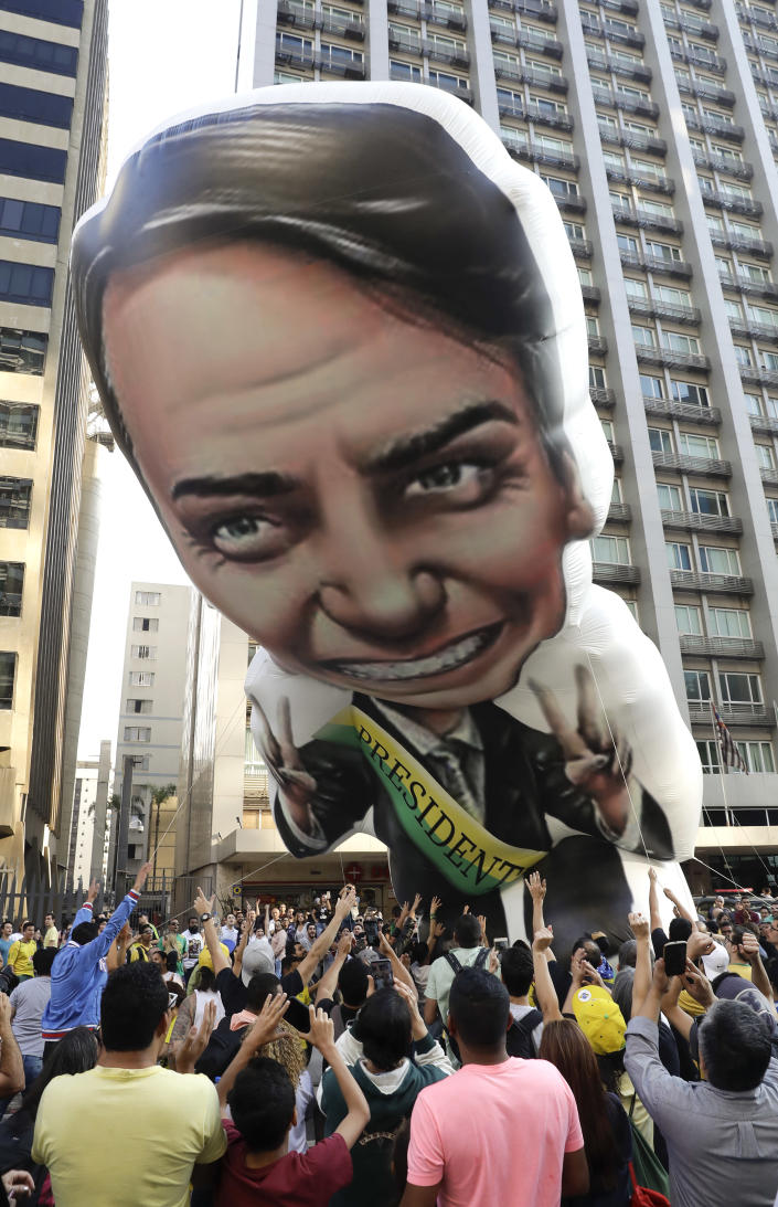 Supporters of Jair Bolsonaro, presidential candidate for the National Social Liberal Party who was stabbed during a campaign event days ago, exhibit a large, inflatable doll in his image as they march along Paulista Avenue to show support for him in Sao Paulo, Brazil, Sunday, Sept. 9, 2018. Brazil will hold general elections on Oct. 7. (AP Photo/Andre Penner)
