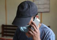 A Myanmar national who said he was a policeman and recently fled to India speaks on his mobile phone at an undisclosed location