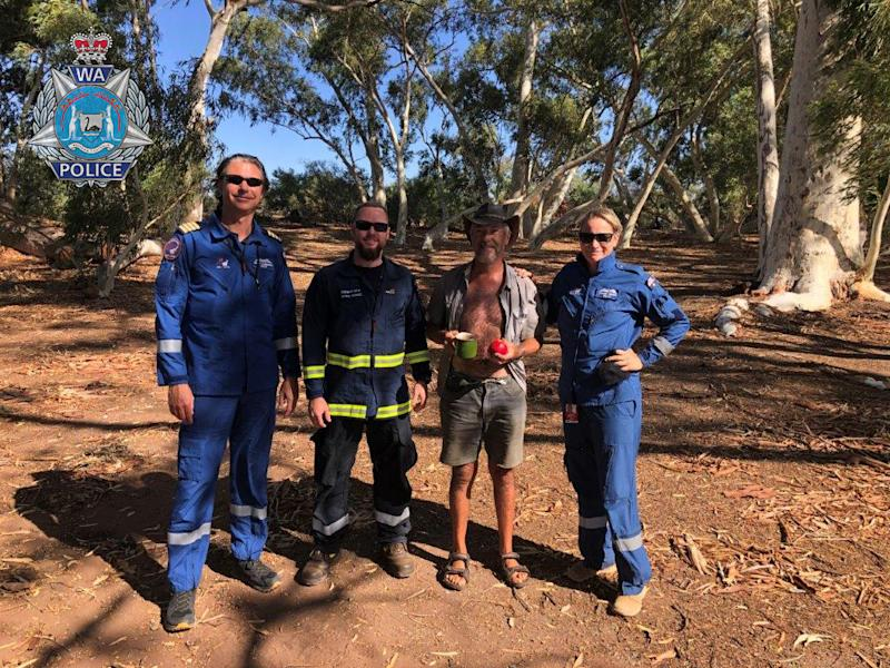 Phillip Blampied with some of his rescuers standing among trees.