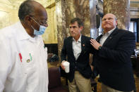Republican Sen. Briggs Hopson, of Vicksburg, center, is congratulated by Senators David Jordan, D-Greenwood, left, and Brice Wiggins, R-Pascagoula, for successfully navigating a resolution to suspend the rules and vote to change the state flag Saturday, June 27, 2020, at the Capitol in Jackson, Miss. The resolution passed and now the House and Senate are expected to pass a bill that removes the current flag and establishes a path forward to getting a new one. Gov. Tate Reeves has already said he would sign whatever flag bill the Legislature decides on. The current flag has in the canton portion of the banner the design of the Civil War-era Confederate battle flag, that has been the center of a long-simmering debate about its removal or replacement. (AP Photo/Rogelio V. Solis)