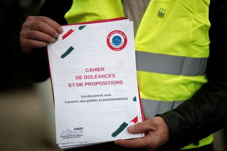 "FILE PHOTO: A yellow vests movement member holds a book of grievances (in French ""Cahier de doleances"") in Flagy, France, January 9, 2019. Picture taken January 9, 2019.  REUTERS/Benoit Tessier/File Photo"