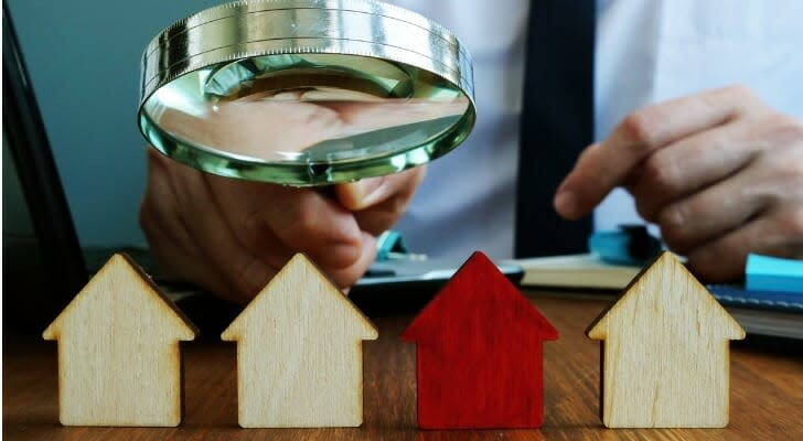 Man using a magnifying glass to inspect model houses