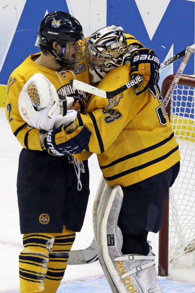 Quinnipiac goalie Eric Hartzell (33) celebrates with defenseman Mike Dalhuisen (2) after a 4-1 win over St. Cloud State during of an NCAA college hockey Frozen Four semifinal game in Pittsburgh, Thursday, April 11, 2013. Quinnipaic advances to the national championship game Saturday against Yale. (AP Photo/Gene J. Puskar)