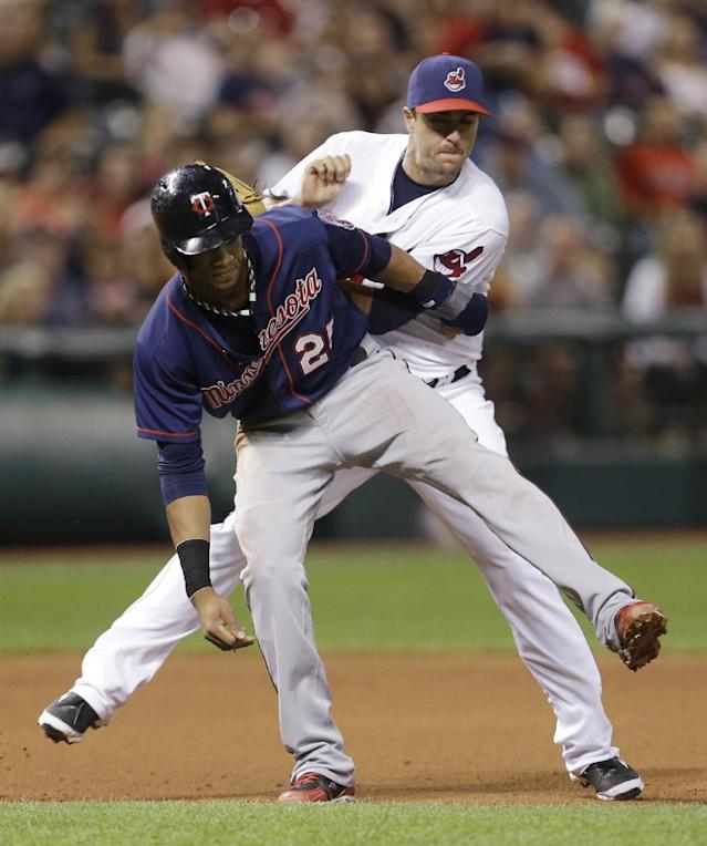 Cleveland Indians third baseman Lonnie Chisenhall, back, tags out Minnesota Twins' Pedro Florimon in the seventh inning of a baseball game, Friday, Aug. 23, 2013, in Cleveland. Florimon was caught stealing third base. (AP Photo/Tony Dejak)