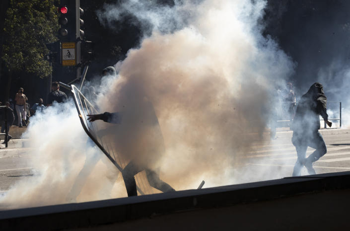 An anti-government demonstrator is engulfed by a cloud of teargas during clashes in Sao Paulo, Brazil, Sunday, May 31, 2020. Police used tear gas to disperse anti-government protesters in Brazil's largest city as they began to clash with small groups loyal to President Jair Bolsonaro. (AP Photo/Andre Penner)
