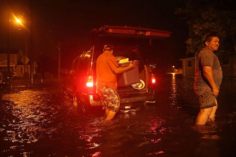 Men pack their belongings after evacuating their house after the Neuse River went over its banks and flooded their street during Hurricane Florence in New Bern, North Carolina, on Thursday.