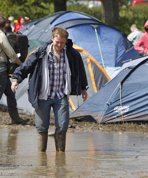 A festival goer walks through the water and mud at the campsite at the Isle of Wight festival on the Isle of Wight England Friday June 22, 2012. Hundreds of music fans have been stranded in their cars overnight after rainstorms caused chaos on travel routes to the Isle of Wight Festival. (AP Photo/Peter Byrne/PA) UNITED KINGDOM OUT