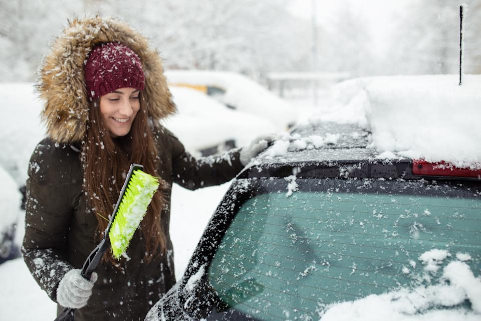 Young woman cleaning snow off her car