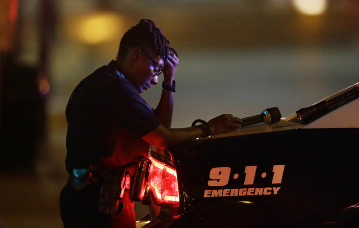 <p>A Dallas police officer, who did not want to be identified, takes a moment as she guards an intersection in the early morning after a shooting in downtown Dallas, July 8, 2016. (Photo: LM Otero/AP) </p>
