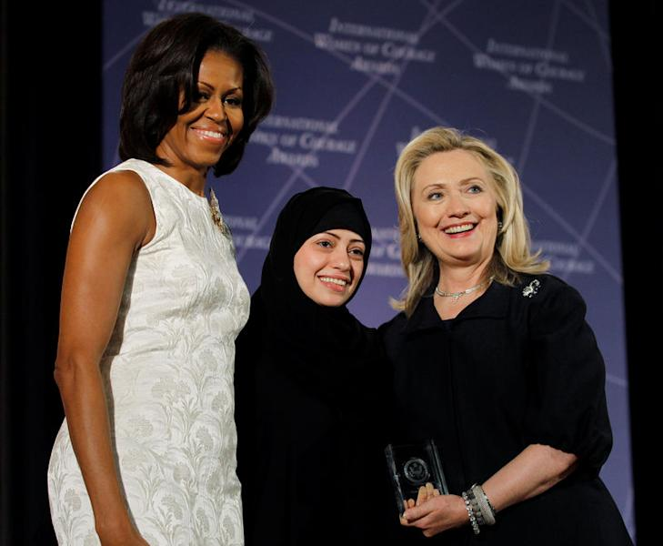 FILE PHOTO: U.S. Secretary of State Hillary Clinton and First lady Michelle Obama (L) congratulate Samar Badawi of Saudi Arabia during the State Department's 2012 International Women of Courage Award winners ceremony in Washington March 8, 2012. REUTERS/Gary Cameron/File Photo
