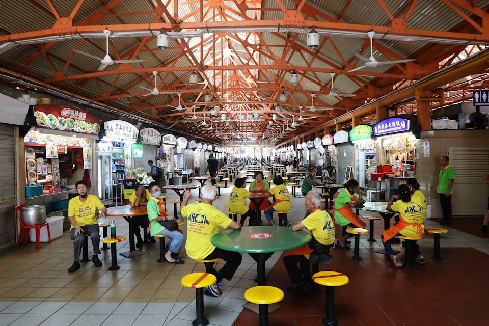 SINGAPORE - APRIL 07: Tables tray cleaners are seen mingling at a hawker centre on April 7, 2020 in Singapore. Singapore government starts closing non-essential workplaces and schools temporarily for a month from today, April 7 to contain the spread of the COVID-19 infections.  (Photo by Suhaimi Abdullah/Getty Images)