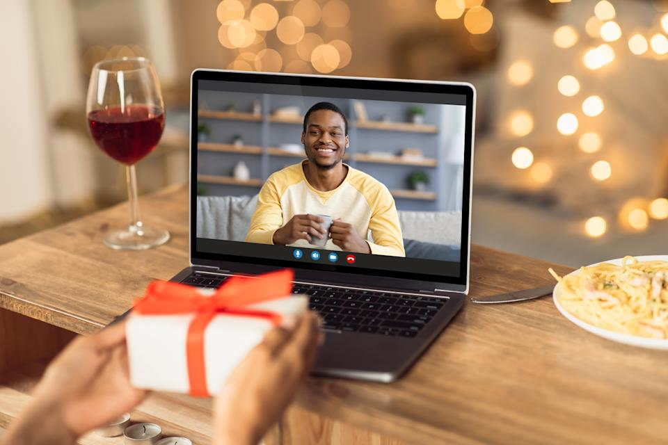Virtual celebration during covid pandemic. Young black woman having online date with her boyfriend or husband, showing wrapped gift box at laptop screen, having wine at home