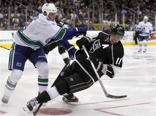 Vancouver Canucks defenseman Kevin Bieksa (3) collides with Los Angeles Kings center Anze Kopitar (11), of Yugoslavia to knock Kopitar to the ice during the second period of Game 3 in a first-round NHL Stanley Cup playoff series in Los Angeles, Sunday, April 15, 2012. (AP Photo/Alex Gallardo)