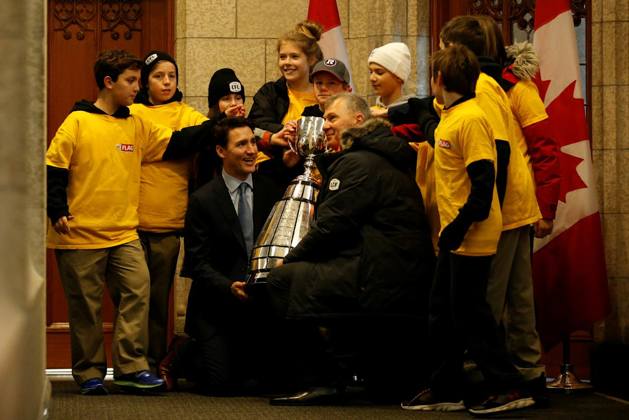 Canada's Prime Minister Justin Trudeau (bottom, L) and CFL commissioner Randy Ambrosie (bottom, R) pose with the Grey Cup trophy along with members of a youth flag football team in front of Trudeau's office on Parliament Hill in Ottawa, Ontario, Canada, November 21, 2017. REUTERS/Chris Wattie