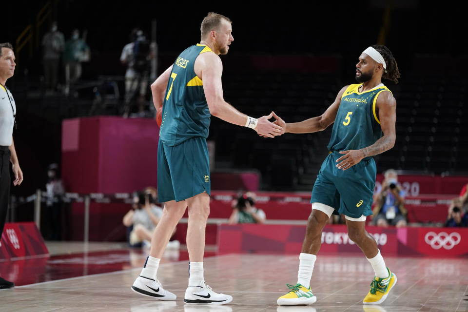 Australia's Joe Ingles, left, and Patty Mills (5) celebrate at the end of a men's basketball preliminary round game against Italy at the 2020 Summer Olympics, Wednesday, July 28, 2021, in Saitama, Japan. (AP Photo/Charlie Neibergall)