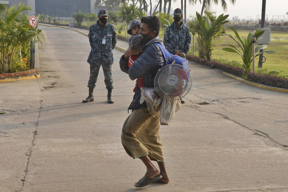 A Rohingya refugee carries a child and walks past soldiers to board a naval vessel to be relocated to the island of Bhasan Char, in Chattogram, Bangladesh, Saturday, Jan. 30, 2021. Authorities in Bangladesh sent a group of Rohingya refugees to a newly developed island in the Bay of Bengal on Saturday despite calls by human rights groups for a halt to the process. The government insists the relocation plan is meant to offer better living conditions while attempts to repatriate more than 1 million refugees to Myanmar would continue. (AP Photo/Azim Aunon)