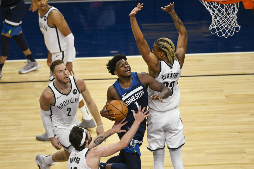 Minnesota Timberwolves guard Anthony Edwards (1) is fouled by Brooklyn Nets forward Nicolas Claxton, right, as Edwards drives past Nets forwards Blake Griffin(2) and Joe Harris during the second half of an NBA basketball game Tuesday, April 13, 2021, in Minneapolis. The Nets won 127-97. (AP Photo/Craig Lassig)