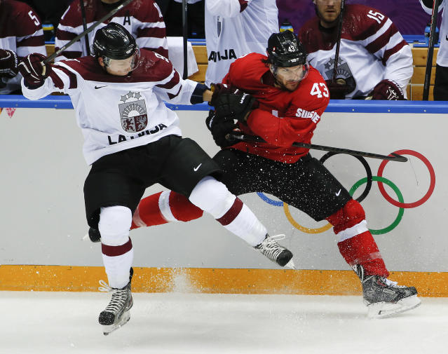 Latvia forward Ronalds Kenins, left, and Switzerland forward Morris Trachsler crash the boards in the second period of a men's ice hockey game at the 2014 Winter Olympics, Tuesday, Feb. 18, 2014, in Sochi, Russia. (AP Photo/Julio Cortez)