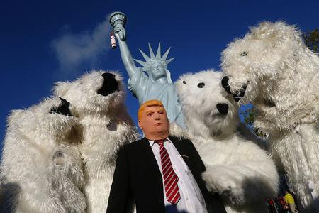 "FILE PHOTO: A protester wearing a mask of U.S. President Donald Trump stand along with other protesters dressed as polar bears during a demonstration under the banner ""Protect the climate - stop coal"" two days before the start of the COP 23 UN Climate Change Conference hosted by Fiji but held in Bonn, Germany November 4, 2017. REUTERS/Wolfgang Rattay/File Photo"