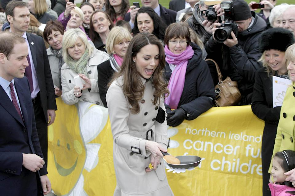 Kate got stuck in as she flipped a pancake at a display by the charity Northern Ireland Cancer Fund for Children outside Belfast City Hall during the couple's visit to Northern Ireland in March 2011. (PA Images)