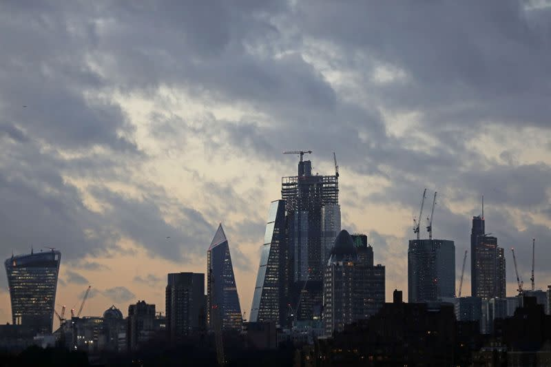 FILE PHOTO: The sun sets behind the Canary Wharf financial district of London
