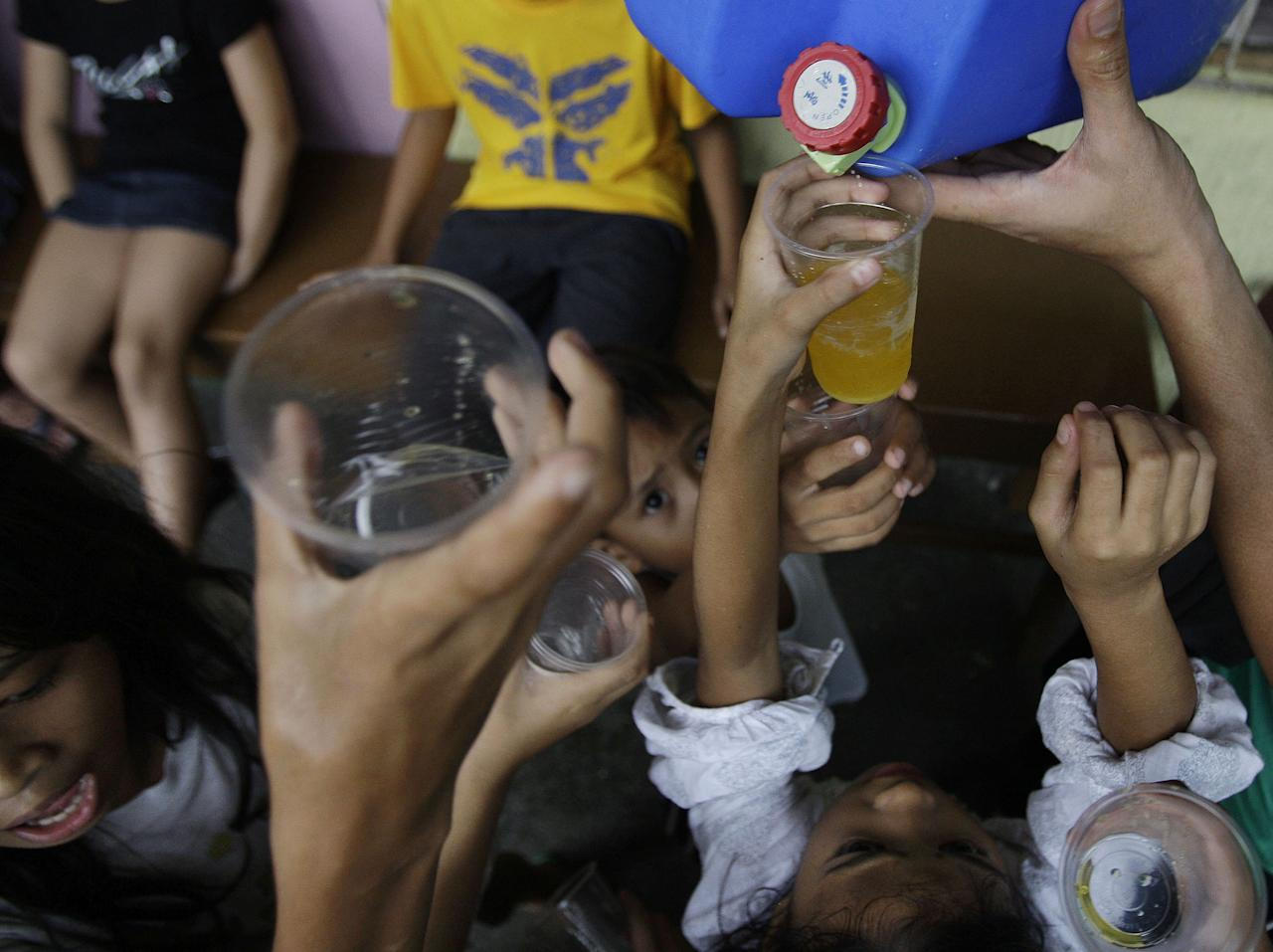 Young evacuees raise plastic cups close to a container to get the last drops of orange juice from private donors at a school that was converted into a temporary evacuation center in suburban Marikina city, east of Manila, Philippines, Friday Aug. 10, 2012. About 2.4 million people in Manila and nearby provinces have been affected, forcing more than 360,000 to seek shelter in government-run evacuation centers, the Office of Civil Defense reported Friday. (AP Photo/Aaron Favila)