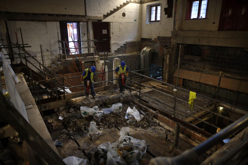 Builders pose for photographers as they carry out work on a new indoor venue at Shakespeare's Globe during an event for the media in London, Tuesday, Nov. 27, 2012. The new venue is named the Sam Wanamaker Theatre after the late American actor-director who spent decades realizing his dream of rebuilding Shakespeare's playhouse. It is due to open in January 2014, and will allow the Globe to hold performances year-round. (AP Photo/Matt Dunham)