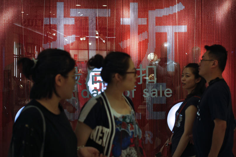People walk by a fashion retailer having promotion sale at a shopping mall in Beijing, Monday, July 15, 2019. China's economic growth sank to its lowest level in at least 26 years in the quarter ending in June, adding to pressure on Chinese leaders as they fight a tariff war with Washington. (AP Photo/Andy Wong)
