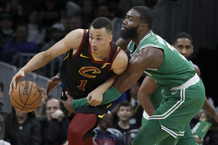 Cleveland Cavaliers Donte Eum, left, guard is fouled by Boston Celtics guard Jaylen Brown, right, in the first half of an NBA basketball game, Friday, Dec. 27, 2019, in Boston. (AP Photo/Elise Amendola)