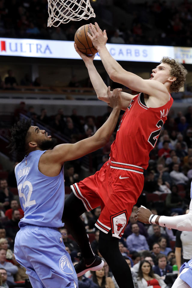 Chicago Bulls forward Lauri Markkanen, right, drives to the basket against Minnesota Timberwolves center Karl-Anthony Towns during the second half of an NBA basketball game in Chicago, Wednesday, Jan. 22, 2020. The Bulls won 117-110.(AP Photo/Nam Y. Huh)