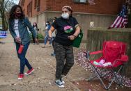 Mayoral Candidate Tishaura Jones. far left, dances with Tracey Clark Jeffries outside the polling place at the corner of Newstead and Laclede Avenues in the Central West End in St. Louis on Tuesday, April 6, 2021. (Sara Diggins/St. Louis Post-Dispatch via AP)