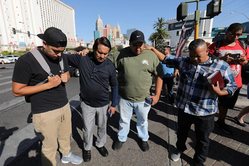 A group of men pray at a makeshift memorial in the middle of Las Vegas Boulevard following the mass shooting in Las Vegas, Nevada, U.S., October 4, 2017.