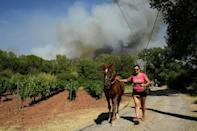 A woman evacuates a horse as smoke rises in the background in Gonfaron, southern France.