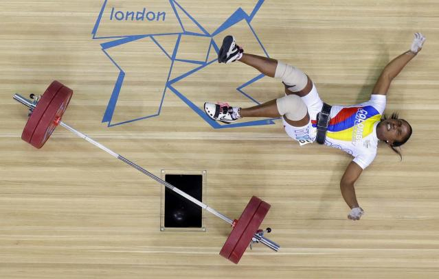 Lina Marcela Rivas of Colombia falls while competing during the women's 58-kg weightlifting competition at the 2012 Summer Olympics, Monday, July 30, 2012, in London. (AP Photo/Ben Curtis)