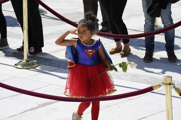 A child in a Supergirl costume pays respects as Justice Ruth Bader Ginsburg lies in repose in front of the US Supreme Court in Washington, DC on September 23, 2020.