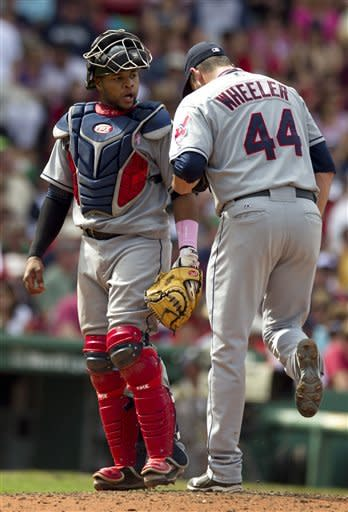 Cleveland Indians catcher Carlos Santana, left, speaks with pitcher Dan Wheeler, right, in the seventh inning of a baseball game against the Boston Red Sox at Fenway Park, in Boston on Sunday, May 13, 2012. The Red Sox defeated the Indians 12-1. (AP Photo/Steven Senne)