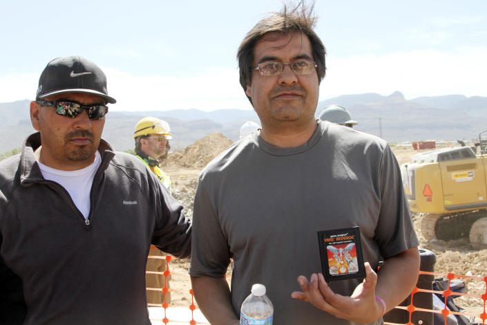 Alamogordo residents Armando Ortega, left, and Raul Ruiz pose for a photograph with a cartridge they found buried in a landfill in Alamogordo, N.M., Saturday, April 26, 2014. Producers of a documentary dug in an southeastern New Mexico landfill in search of millions of cartridges of the Atari 'E.T. the Extra-Terrestrial' game that has been called the worst game in the history of video gaming and were buried there in 1983. (AP Photo/Juan Carlos Llorca)