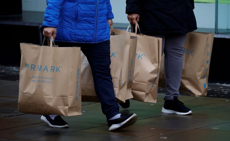 FILE PHOTO: Shoppers carry bags from Primark at the start of the Boxing Day sales amid the outbreak of the coronavirus disease (COVID-19) in Manchester