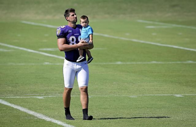 Baltimore Ravens tight end Dennis Pitta carries his son Decker on the field after an NFL football training camp practice on Saturday, July 26, 2014, in Owings Mills, Md. (AP Photo/Patrick Semansky)