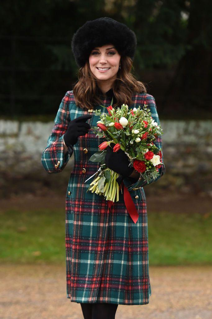 <p>Kate looked festive on Christmas Day in a red and green plaid coat paired with black gloves and a fur hat. </p>